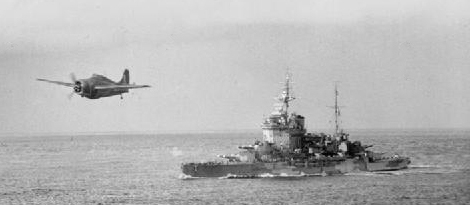 A Grumman Martlet from HMS Formidable flying near HMS Warspite