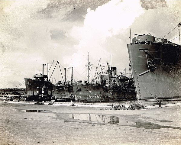 USN APA transports docked in the only peer of Saipan in late summer 1944